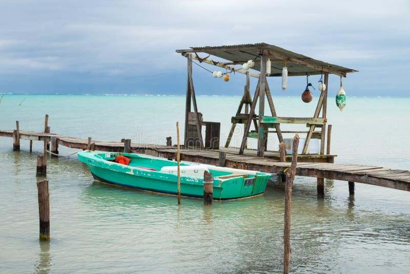 Bote pequeño, amarrando los posts, las boyas y el mar tropical cubierto fotografía de archivo
