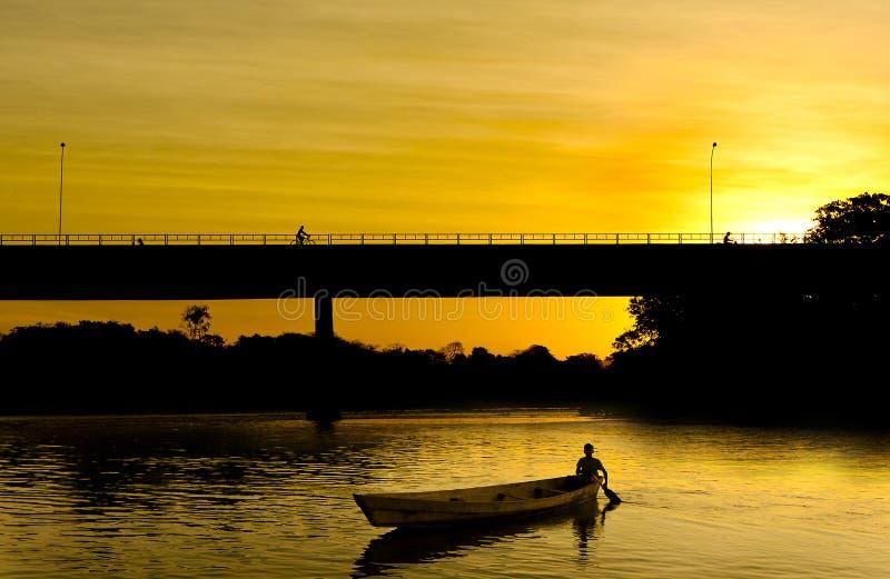 Bote pequeño en la puesta del sol imagen de archivo