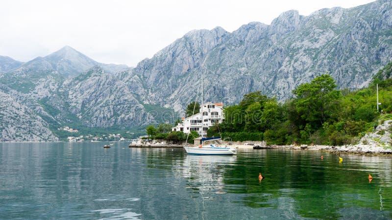 Bote pequeño solo en un pueblo del pescador en la bahía de Kotor Lago rodeado por las montañas grandes grises y los cepillos verd foto de archivo