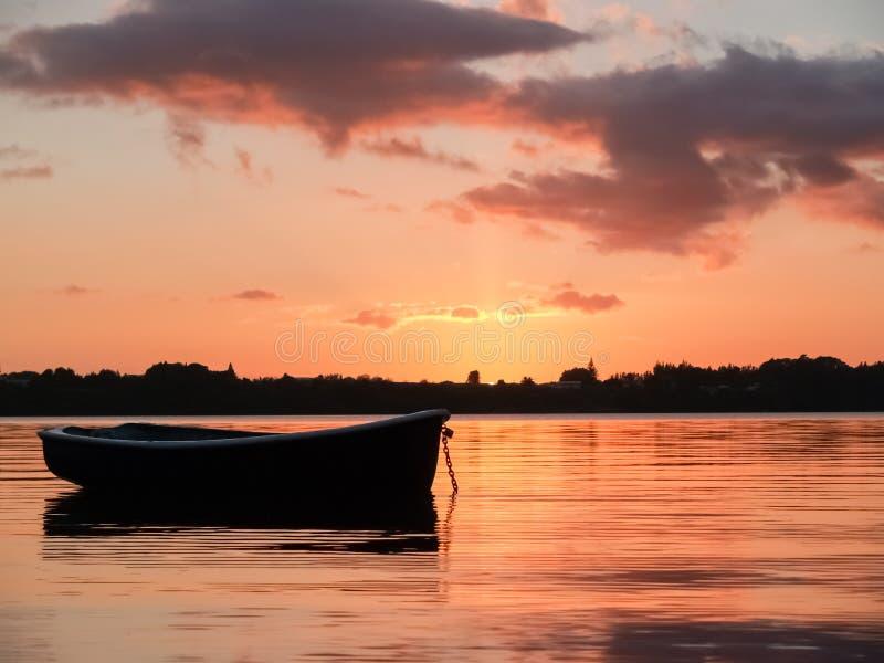 Bote pequeno à tona e mostrado em silhueta na água vermelha do porto no sunr fotografia de stock royalty free