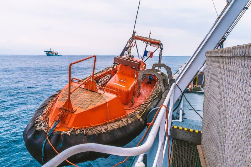 Bote salvavidas o bote de salvamento de FRC en el buque en el mar la nave del dsv está en fondo imagen de archivo