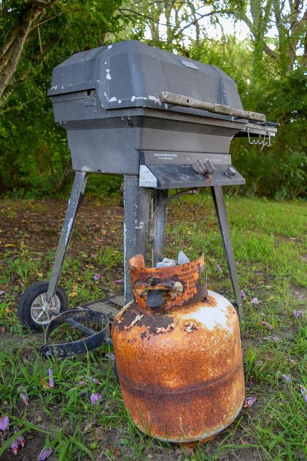 Bote viejo y muy oxidado del propano y parrilla al aire libre fotos de archivo
