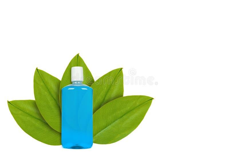 Botella azul con el enjuague en el fondo de hojas verdes Aislado en blanco noción del origen natural fotos de archivo libres de regalías