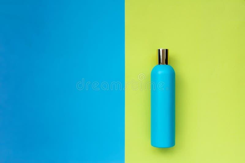 Botella azul en un fondo amarillo-azul Espacio vac?o bajo texto envase de plástico limpio imagen de archivo
