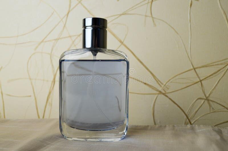 Botella azul, hermosa, de cristal con el cologne, agua de retrete, perfume en un fondo del papel pintado beige imagen de archivo