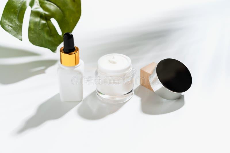 Botella blanca y tarro poner crema, maqueta del suero de la marca de producto de belleza Opini?n superior sobre el fondo blanco foto de archivo