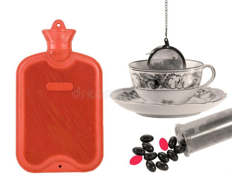Botella caliente, taza de té y pastillas. imagenes de archivo