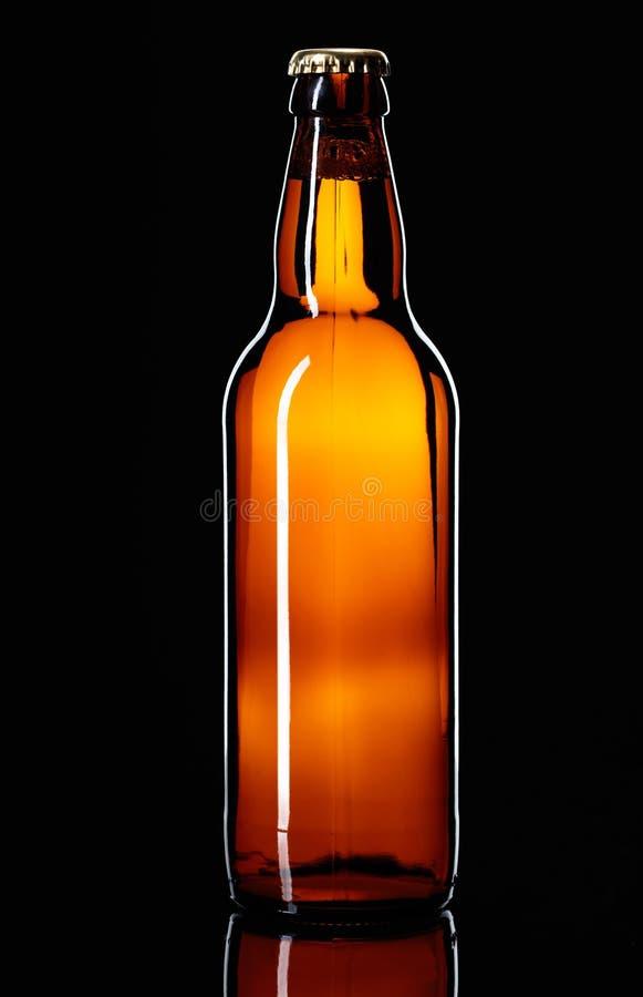 Botella cerrada de cerveza en un fondo negro imágenes de archivo libres de regalías