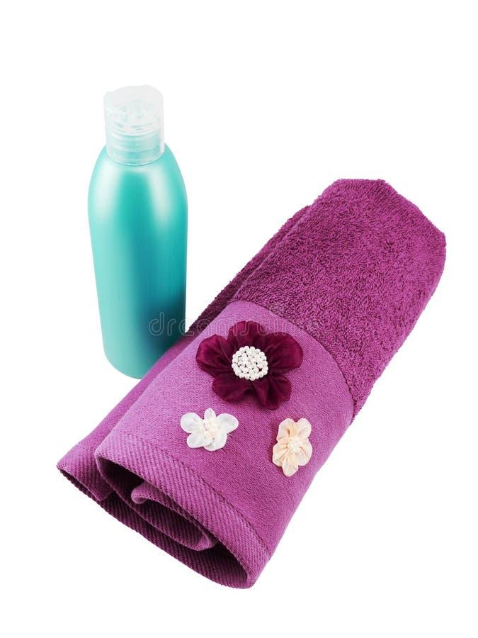 Botella ciánica en blanco del champú y toalla púrpura imagen de archivo