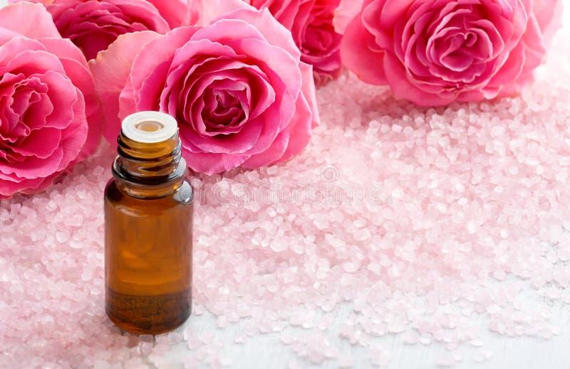 Botella con aceite esencial, cristales de la sal del balneario y rosas rosadas imagenes de archivo