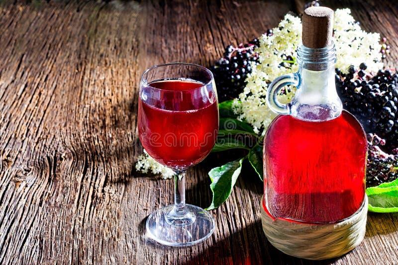 Botella con el jugo de la baya del saúco y las bayas frescas en la tabla de madera fotos de archivo libres de regalías