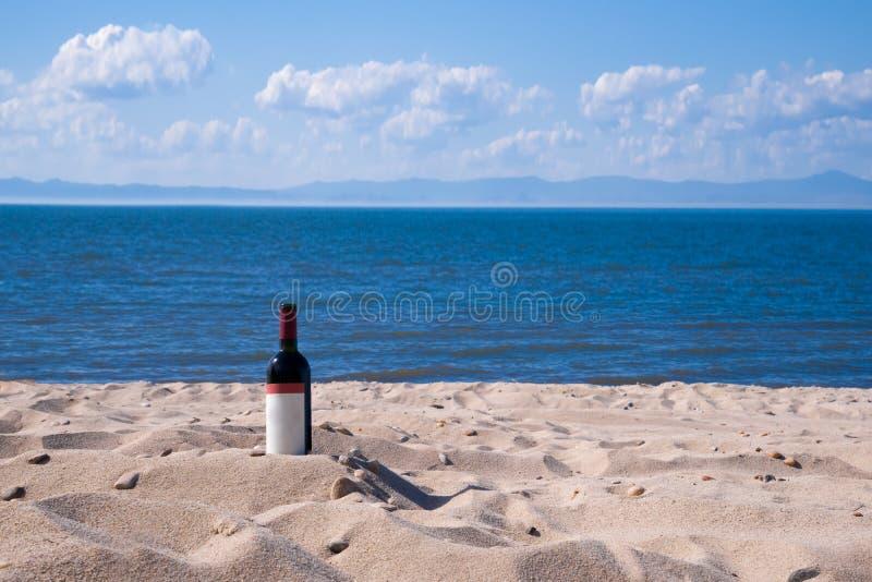Botella con el vino rojo en la playa en un día soleado del verano Arena amarilla, nubes blancas, cielo azul y mar azul en fotografía de archivo