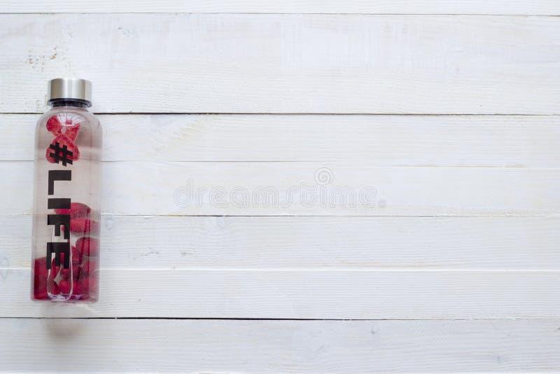 Botella con la bebida de restauración, agua con las rebanadas de la fresa, con vida del hashtag en el fondo blanco imagen de archivo libre de regalías