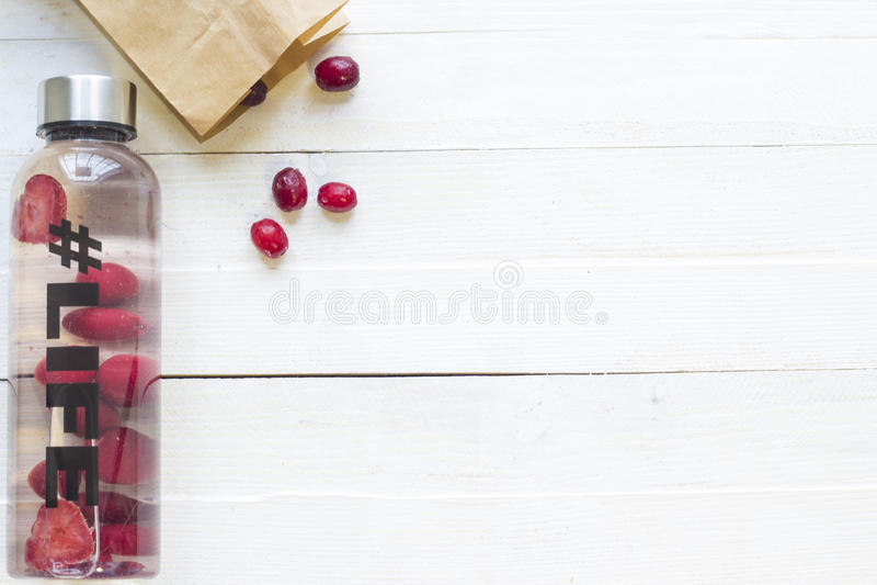 Botella con la bebida de restauración, agua con las rebanadas de la fresa, con vida del hashtag y el paquete con las bayas congel fotografía de archivo
