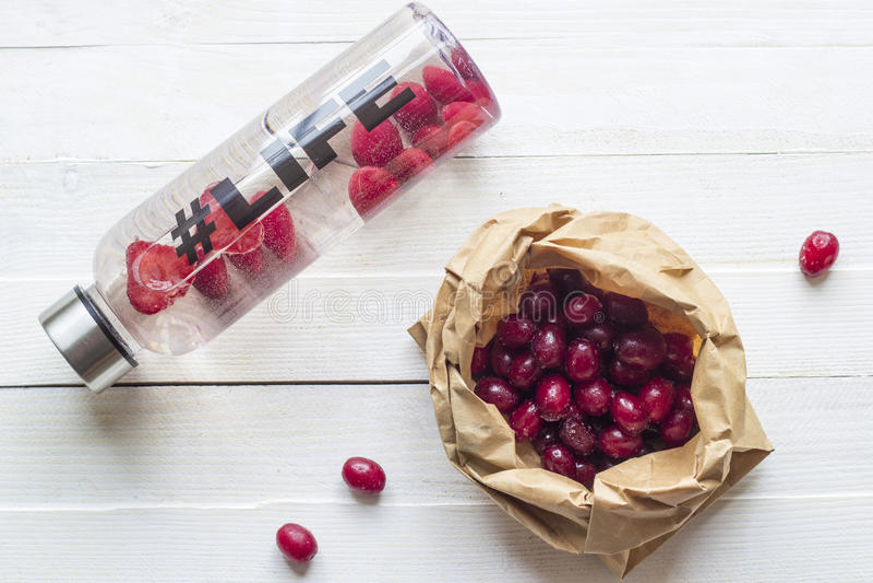 Botella con la bebida de restauración, agua con las rebanadas de la fresa, con vida del hashtag y el paquete con las bayas en fon fotografía de archivo libre de regalías