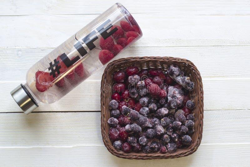 Botella con la bebida de restauración, agua con las rebanadas de la fresa, con vida del hashtag y la cesta con las bayas congelad imagenes de archivo