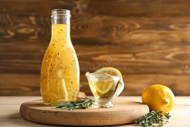 Botella con la salsa, los limones y las hierbas sabrosos en la tabla de madera foto de archivo