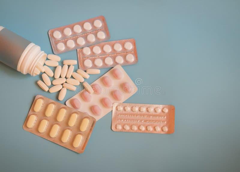 Botella con las píldoras y las ampollas con las píldoras y cápsulas en fondo azul fotos de archivo libres de regalías