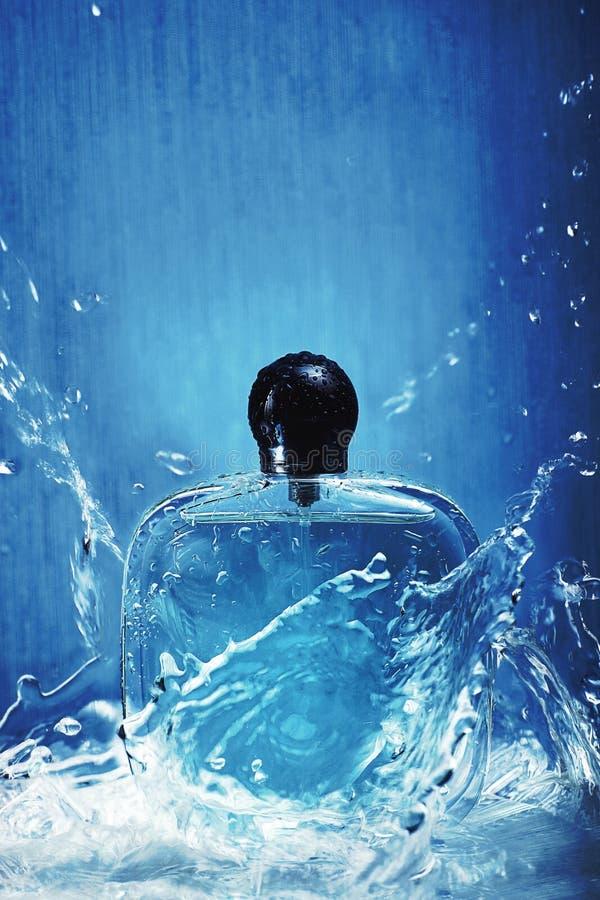 Botella con perfume en un fondo azul con agua y los esprayes fuertes fotos de archivo libres de regalías
