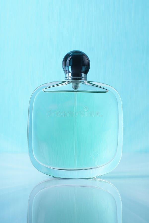 Botella con perfume en un fondo azul con la reflexión fotos de archivo libres de regalías
