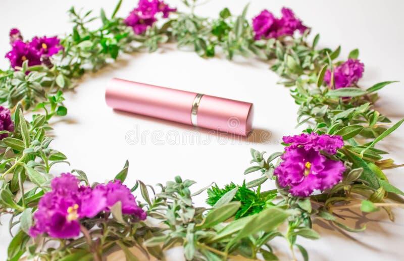 Botella cosmética con colores y pétalos en un fondo blanco del escritorio, una visión superior, calificando para arriba y un e fotografía de archivo