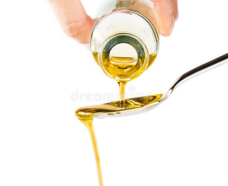 Botella de aceite de oliva virginal adicional que vierte sobre una cuchara aislada en el fondo blanco fotografía de archivo libre de regalías
