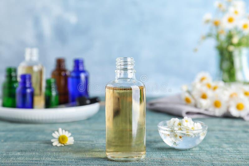Botella de aceite esencial, de cuenco y de tabla de las flores foto de archivo libre de regalías