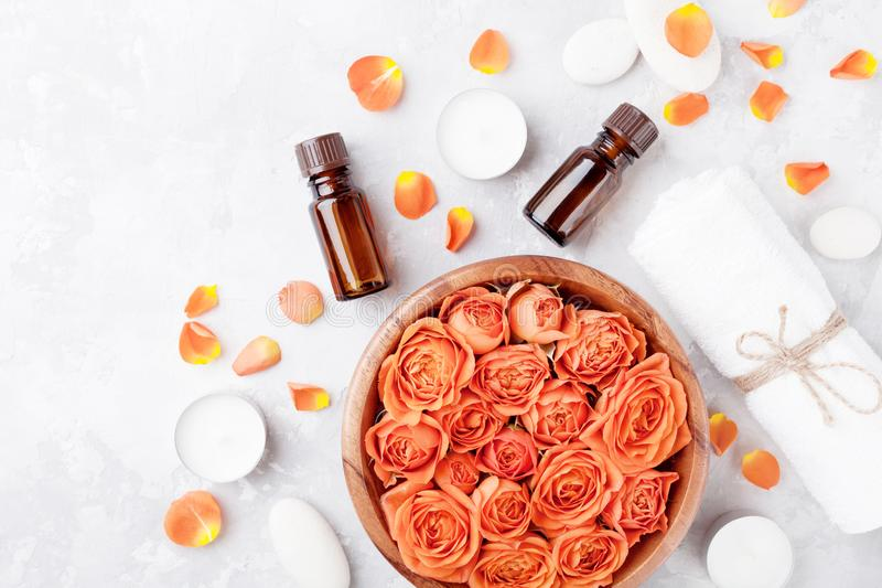 Botella de aceite esencial, flor color de rosa en cuenco, toalla y velas en la opinión de sobremesa de piedra Balneario, aromathe foto de archivo libre de regalías
