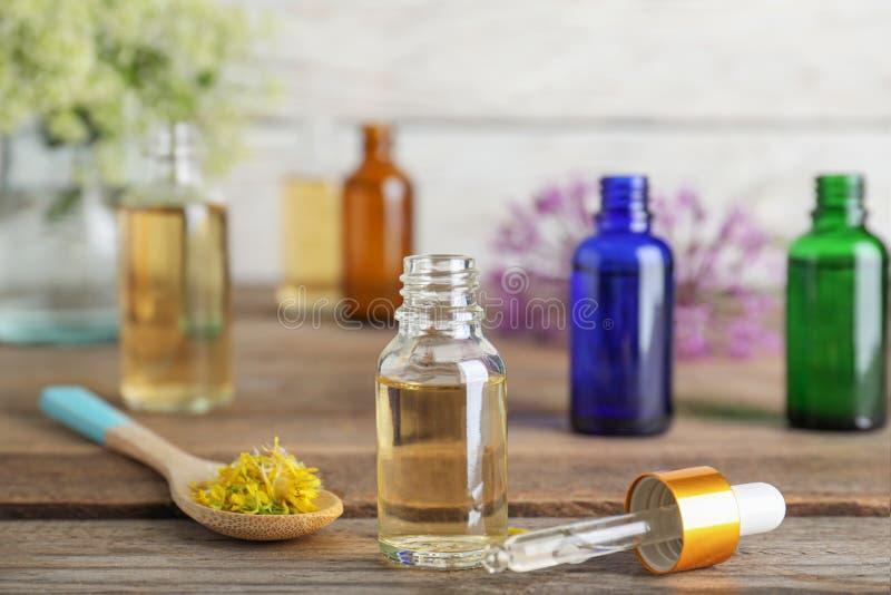 Botella de aceite esencial, de pipeta y de cuchara con las flores en la tabla de madera foto de archivo libre de regalías