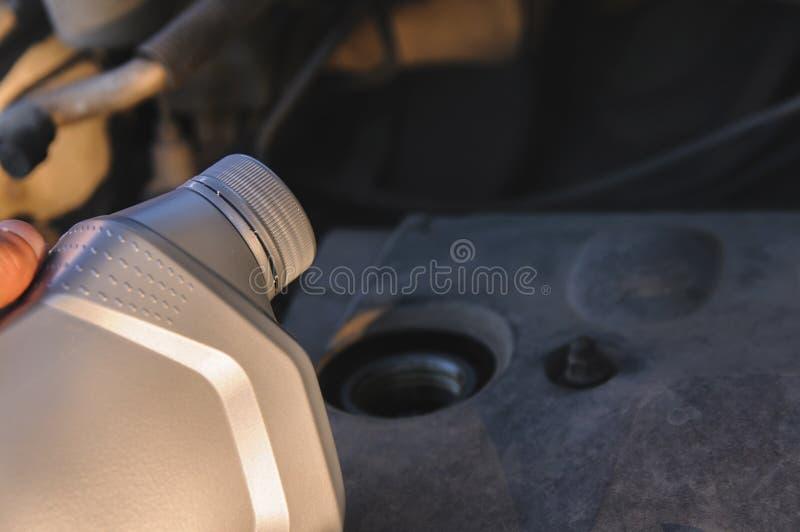 Botella de aceite de motor en el fondo del motor imagenes de archivo