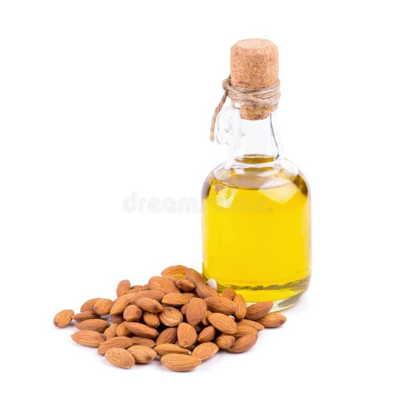 Botella de aceite y de almendras de almendra aislados en el fondo blanco fotografía de archivo