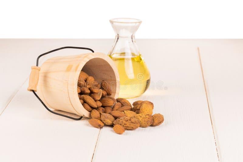 Botella de aceite y de almendras de almendra en el fondo de madera blanco fotografía de archivo libre de regalías