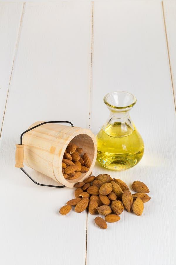 Botella de aceite y de almendras de almendra en el fondo de madera blanco foto de archivo