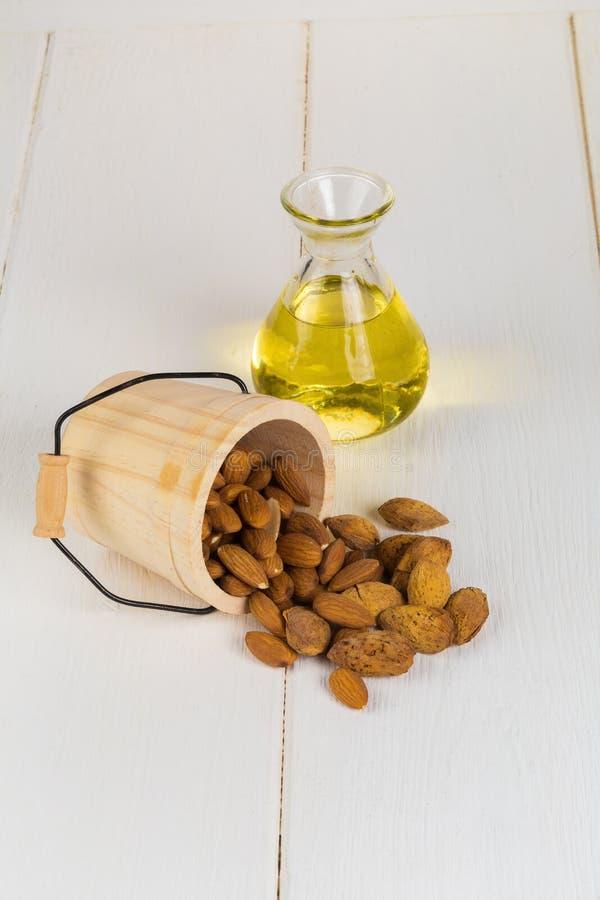 Botella de aceite y de almendras de almendra en el fondo de madera blanco fotos de archivo