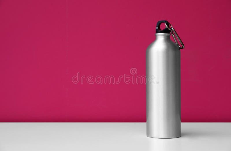 Botella de agua de aluminio para los deportes en fondo del color imagen de archivo libre de regalías