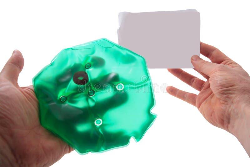 Botella de agua caliente médica y hoja de papel vacía en manos imagen de archivo libre de regalías