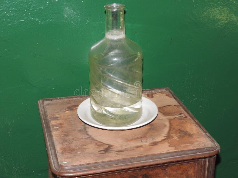 Botella de agua de cristal vieja en la tabla en fondo verde fotografía de archivo libre de regalías