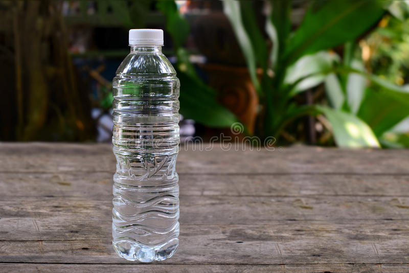 Botella de agua en la tabla de madera vieja en el jardín imagen de archivo libre de regalías