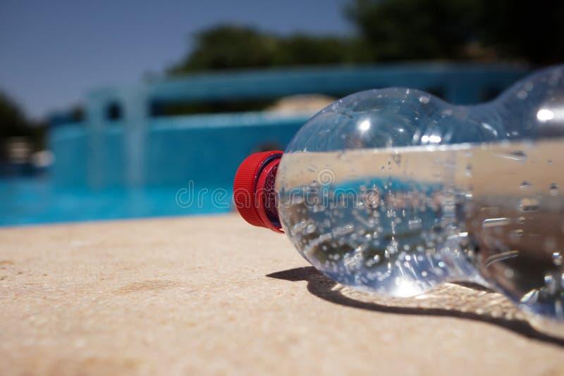 Botella De Agua En Poolside Imágenes de archivo libres de regalías