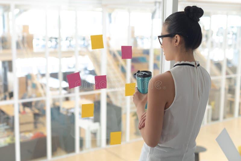 Botella de agua femenina de la tenencia del ejecutivo de operaciones y mirada a través de ventana en una oficina moderna foto de archivo