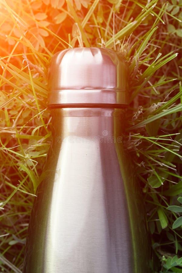 Botella de agua inoxidable del termo, color azul Maqueta aislada en fondo de la hierba verde con efecto de la luz del sol Vacío d foto de archivo