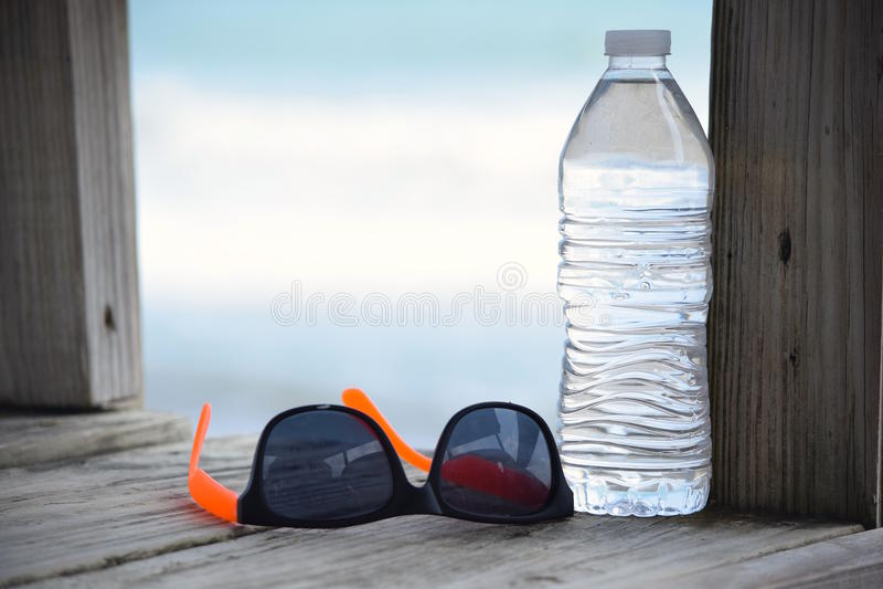 Botella de agua quebradiza y pares de gafas de sol en paseo marítimo foto de archivo libre de regalías
