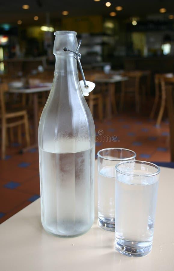 Botella de agua y vidrios fotos de archivo