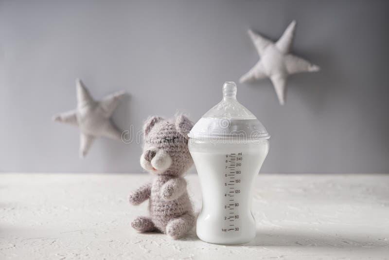 Botella de alimentación de preparado para bebés con el juguete del oso de peluche en la tabla blanca imagen de archivo libre de regalías