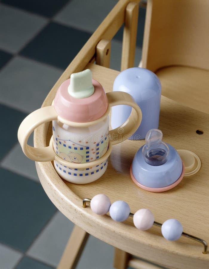 Botella de bebé por completo de leche en una alta silla fotografía de archivo