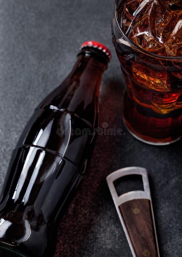 Botella de bebida de la soda de la cola y vidrio con los cubos de hielo al lado del abrelatas en fondo de piedra negro fotos de archivo libres de regalías