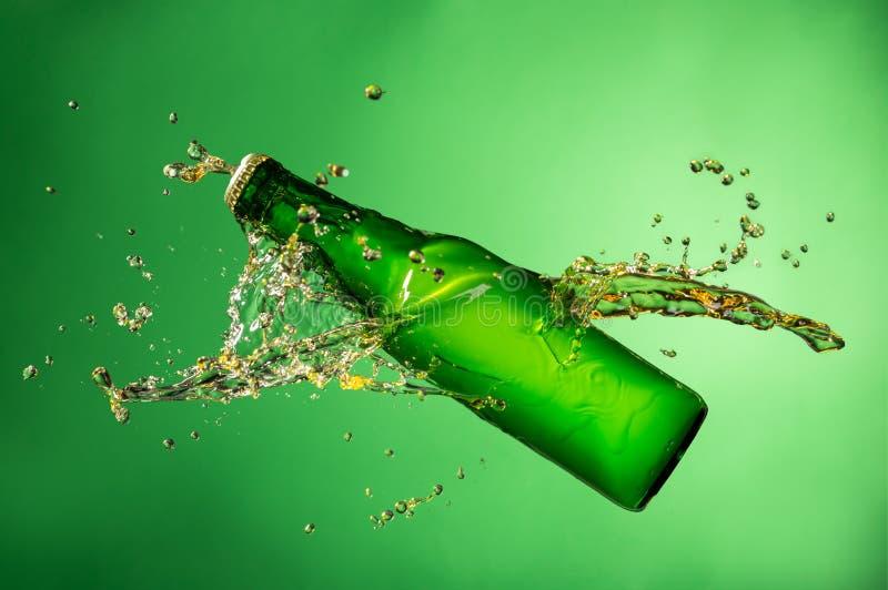 Botella de cerveza con el chapoteo, en fondo verde fotos de archivo libres de regalías