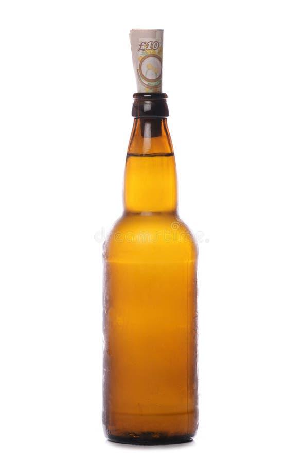 Botella de cerveza con el dinero fotos de archivo
