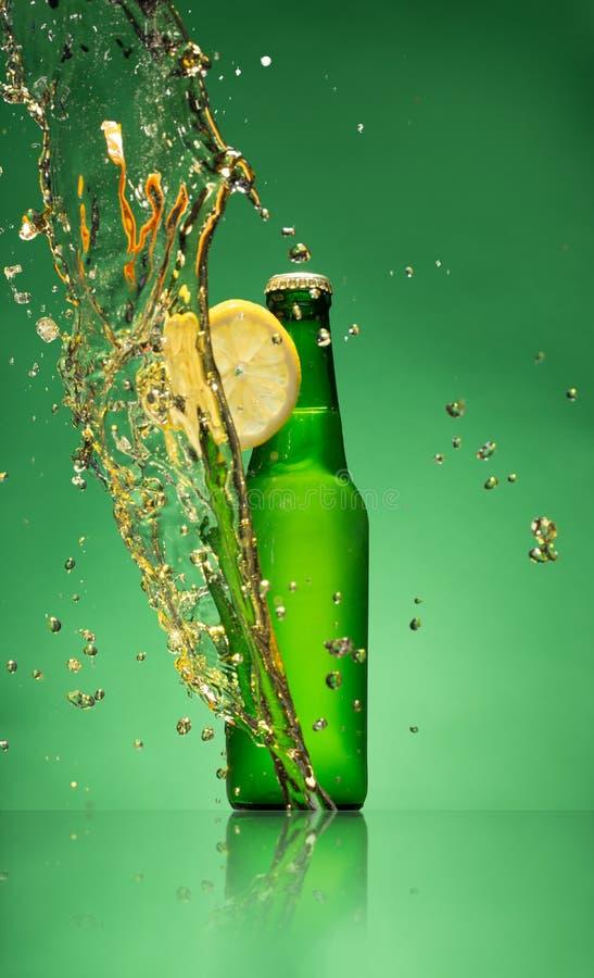 Botella de cerveza de la fruta con el chapoteo, en gree imagen de archivo libre de regalías