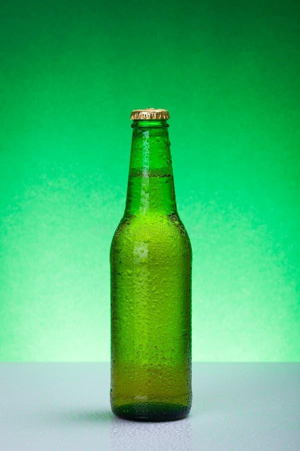 Botella de cerveza en blanco verde mojada foto de archivo libre de regalías